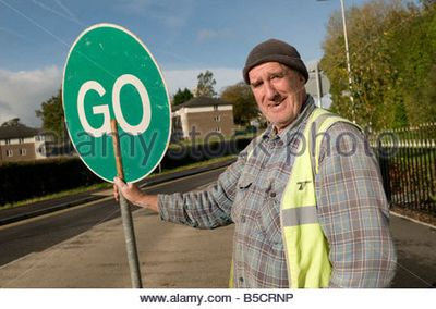 man-controlling-traffic-with-a-hand-held-rotating-stop-go-sign-on-b5crnp